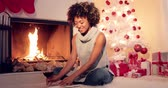 ribbon : Smiling stylish young woman enjoying a book at Christmas sitting on the floor alongside a roaring fire in front of a decorated tree and gifts Stock Footage