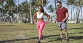 wellbeing : Sportive fit black woman doing dynamic lunges with help of personal instructor in green tropical park on green lawn. Stock Footage