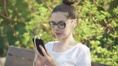 searching : Attractive female in glasses using smartphone with headphones sitting on park bench and looking at camera