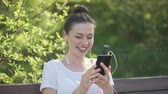videochat : Smiling attractive female sitting on park bench in headphones and talking by videochat on smartphone
