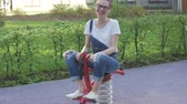 булочка : Young smiling female in eyeglasses riding spring toy on playground and looking at camera.