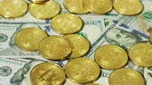 befektetés : Close-up view of golden coins with sign of bitcoin cryptocurrency arranged on top of new US dollar bills.
