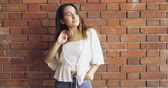 parede de tijolos : Smiling sexy trendy young woman standing in front of a red brick wall with her hands in her pockets in a relaxed pose Stock Footage