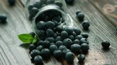 elszórt : Closeup fresh appetizing blueberry scattering out of glass jug on wooden desk with water drops