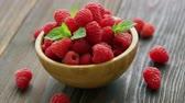 parcela : Closeup fresh red raspberry with green leaves in wooden bowl on dark table Stock Footage