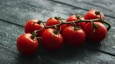 промывали : Closeup branch with ripe cherry tomatoes on dark wooden table