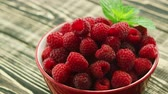 framboesa : From above closeup shot of fresh ripe raspberry with green leaf in bowl on wooden table