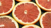cytrusy : Closeup of composed round slices of cut grapefruit of bright ret color arranged together on glass surface Wideo