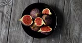 figa : From above view of black round plate with delicious ripe figs cut into halves and served on gray wooden table