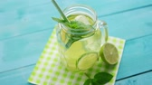 citrus fruit recipes : From above shot of jar glass with lime cocktail and mint leaves served on green napkin with straw Stock Footage
