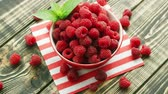 szolgált : From above shot of bowl full with red raspberries and served on napkin on wooden table