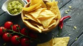 çili : From above view of wooden bowl filled with golden crispy nacho chips on wooden table with lime and chili pepper