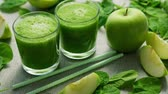 spinach : Layout of few glasses filled with green smoothie and served on table with green apples and spinach leaves