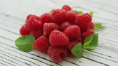 framboesa : Closeup shot of composed heap of bright ripe raspberry with mint leaves on wooden table