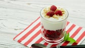 natural yogurt : Glass filled with fresh red raspberry and yogurt topped with crispy granola and berries served on napkin with spoon