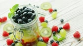 słoik : Closeup shot of glass jar filled with fresh fruit and berry mix served on wooden table with spilled berries around