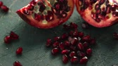 rubi : Closeup shot of halves of delicious pomegranate and pile of ruby pomegranate seeds on table