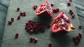 točit : Composed halves of ripe pomegranate with bright shiny ruby-colored seeds on rough board