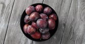 colorful : Top view of round bowl filled with ripe wet purple plums and served on gray wooden table Stock Footage