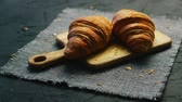 kruvasan : Two fresh croissants lying on cutting board on textile napkin on background of black table Stok Video