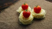 erişte : From above view of spaghetti rolled in balls with fresh tomatoes on top placed on textile tablecloth Stok Video
