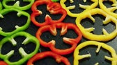 bell pepper ring : Closeup of composed layer of multicolored rings of cut bell peppers on wet surface