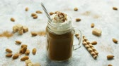 davranır : Glass jar with sweet caramel drink garnished with whipped cream and served with straw on table among nuts