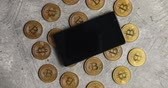 monetário : Top view of golden bitcoins composed on gray surface with modern smartphone on top