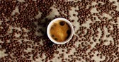 brewed : Top view of mug with black coffee on canvas textile covered with roasted coffee beans Stock Footage