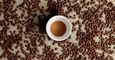 минималист : Flat lay of white cup with ground coffee powder on canvas textile with roasted coffee beans around