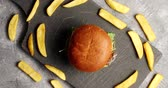 hamburger : Top view of fresh burger with golden bun and fries composed around in circle on board