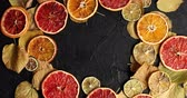 citrus fruit recipe : From above shot of arranged wreath on black surface with dry leaves and dry citrus slices