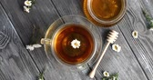 rumianek : Top view of glass mug with herbal tea and camomile on wooden table with jar of honey