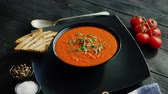 fesleğen : From above view of tomato soup in black bowl sprinkled with herb served with crisp bread on wooden background