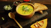 szolgált : From above view of yellow pumpkin soup served in bowl with spoon and bread laid near on wooden cutting board