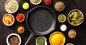 kind : From above view of black pan placed in middle with many bowls of spices around on wooden background