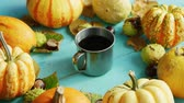 squash : From above view of metal cup of coffee surrounded by orange pumpkins on blue wooden background Stock Footage