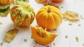 squash : From above view of orange ripe pumpkins laid on wooden background and decorated with withered leaves