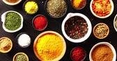 выбор : From above view of many bowls with spices of different kind on black wooden background