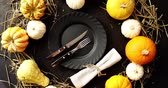 guardanapo : From above view of plate and cutlery with pumpkins of different size placed around on black background