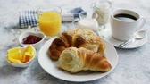 marmelat : Torn soft and delicious croissant on white plate served with coffee and orange juice and marmalade on marble table