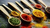 curry : Closeup shot of wooden spoons with various aromatic spices lying on black lumber tabletop in kitchen Stock Footage