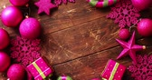 фуксия : From above shot of assorted Christmas decorations of bright fuchsia color forming border on scratched wooden tabletop Стоковые видеозаписи