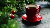 koraliki : Closeup shot of small cup of fresh hot drink standing on lumber tabletop near fresh conifer branches decorated with small red beads