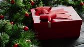 miçanga : Closeup shot of lovely Christmas gift box lying on dark wooden tabletop near green conifer branches decorated with small red beads