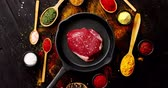 rozmaring : From above view of piece of fresh meat on black pan with different spices in spoons laid near on wooden background Stock mozgókép
