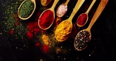 curry : From above view of different sort of colorful spices placed in spoons on wooden background