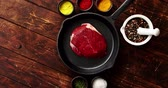 malta : From above view of piece of raw meat laid on black pan surrounded by bowls with colorful spices on wooden background Dostupné videozáznamy