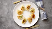 recheado : Fried dumplings with meat filling sprinkled with fresh chive on a white plate. Top view on gray stone background