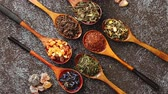 ceylon : Spoons with different types of dry tea leaves on rusty dark background. Top view. Stock Footage